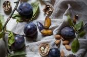 Prunes with leafs, walnuts, almonds on rustic background with jute napkin — Stock Photo