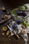 Prunes with leafs and walnuts on rustic background with wooden table and knife — Stock Photo