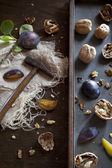 Prunes with waltnuts on rustic background with wooden table and little hammer — Stock Photo