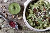 Italian handmade pasta with pesto basil green sauce with pink peppercorn and walnuts on bowl — Stock Photo