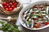 Fresh raw sardines on casserole with cherry tomatoes slices, parsley, garlic and potatoes — Stock Photo