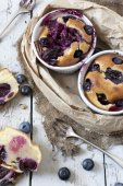 Two clafoutis with blueberries and cherries on ceramic ramekins and cake slices on rustic white vintage background — Stock Photo