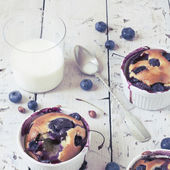 Vintage polaroid instagram of clafoutis with blueberries and cherries on ceramic ramekins on rustic white vintage background — Stock Photo