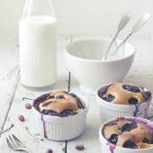 Vintage polaroid instagram of clafoutis with blueberries and cherries on ceramic ramekins on rustic white vintage background with milk bottle — Stock Photo