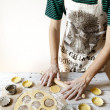 Bearded young man with apron making shortcrust pastry for little tart on molds on rustic background with rolling pin and flour on table — Stock Photo #57742555