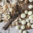 Bio small baby golden onions with peel and some peeled on vintage rustic background with burlap and knife — Stock Photo #59709583