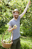 Young bearded smiling boy farmer who gathers pears from trees with straw hat and basket — Stock Photo