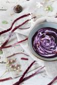 Purple carrot cream soup with sour milk cream and pink peppercorn on bowl on rustic vintage background with carrot peels — Photo