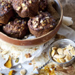 Homemade rustic muffins with pumpkin chocolate and oat flakes on big bowl with vintage strainer full of pumpkin seed — Stock Photo #60589557