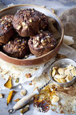 Homemade rustic muffins with pumpkin chocolate and oat flakes on big bowl with vintage strainer full of pumpkin seed — Stock Photo