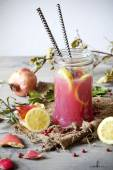 Pomegranate and lemon smoothie on glass jar with two striped straw on rustic background — Stock Photo