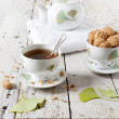 Tea on cup with teapot and amaretti sweets on white table with gingo biloba leaves — Stock Photo #60655129
