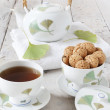 Tea on cup with teapot and amaretti sweets on white table with gingo biloba leaves — Stock Photo #60655131