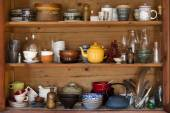 Ceramics and kitchen equipment on rustic and country style wooden shelves — Stock Photo