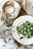 Homemade spinach dumplings with sage leafs and flowers on plate on rustic background with old strainer with white flour — Stock Photo