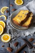 Two slices of citrus cake on plate on table with pecan walnuts and orange slices and little hammer — Stock Photo