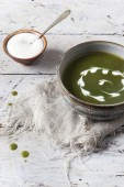 Homemade peas and spinach cream soup with sour cream on bowl on rustic table with frayed cloth — Stock Photo