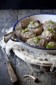 Stuffed mushrooms on vintage enamelled tin on rustic wooden table with frayed cloth — Stock Photo