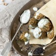 Homemade falafel balls with yogurt sauce on paper cornet and spoon on vintage tray with sesame seed — Stock Photo #60848307