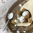 Homemade falafel balls with yogurt sauce on paper cornet and spoon on vintage tray with sesame seed — Stock Photo #60848361