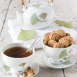 Tea on cup with teapot and amaretti sweets on white table with gingo biloba leaves — Stock Photo #60848935