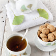 Tea on cup with teapot and amaretti sweets on white table with gingo biloba leaves — Stock Photo #60848967