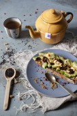 Wholemeal vegan toast with avocado slices and black sesame seeds on table with teapot and frayed napkin — Stock Photo