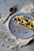 Wholemeal vegan toast with avocado slices, lemon, orange peel, pink pepper and black sesame seeds on plate with frayed napkin — Stock Photo