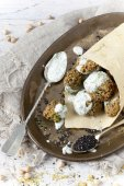 Homemade falafel balls with yogurt sauce on paper cornet and spoon on vintage tray with sesame seed — Stock Photo
