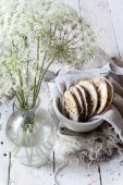 Homemade alternative cookies on bowl on white wooden table with wildflowers on vase and frayed jute cloth — Stock Photo