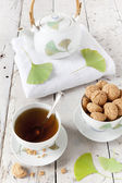 Tea on cup with teapot and amaretti sweets on white table with gingo biloba leaves — Stock Photo