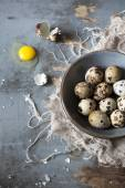 Quail eggs on bowl on blue wooden table with frayed cloth and one broken egg — Stock Photo