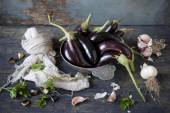 Group of long eggplants on vintage plate on wooden table with garlic and parsley and frayed cloth — Stock Photo