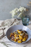 Homemade pumpkin dumplings on plate with thyme and parmesan on rustic table with flowers — Stock Photo