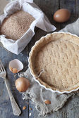 Raw wholemeal dough for tart on ceramic mold for quiche with eggs and flour on table with napkin and fork — Stock Photo