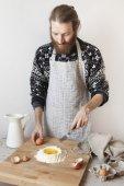 Junger bärtiger stilvollen Mann in der Küche mit Schürze machen Teig für Pasta mit Mehl und Eiern — Stockfoto
