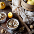 Two portions of apple crumble with almonds on rustic wooden table, whole apples and lighted candle — Stock Photo #64834879