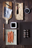 Overhead shot of prepared hosomaki sushi and ingredients on table — Stock Photo