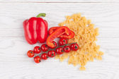 Tomatoes, red pepper and macaroni on table — Stock Photo