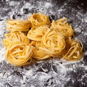 Raw pasta tagliatelle on table — Stock Photo