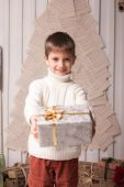 Little boy hold present in Christmas interior — Stock Photo
