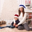 Little boy with mom posing in Christmas interior — Stock Photo #61959421