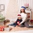 Little boy with mom posing in Christmas interior — Stock Photo #61959425