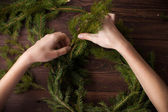 Making Christmas wreath with hands on wooden background — Stock Photo