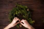 Weihnachtskranz mit Händen machen auf hölzernen Hintergrund — Stockfoto