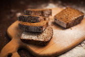 Plátky žitného chleba na řezací deska záběr na stole — Stock fotografie