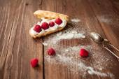 Eclair with fresh raspberries on wood table, confectioner table — Stock Photo