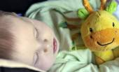Beautiful little baby sleeping with a toy — Foto de Stock