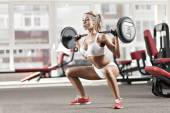 Woman doing exercise with barbell — Stock Photo