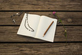 Blank open notebook, wooden pencil and Catholic chaplet for pray on wooden background — Stock Photo
